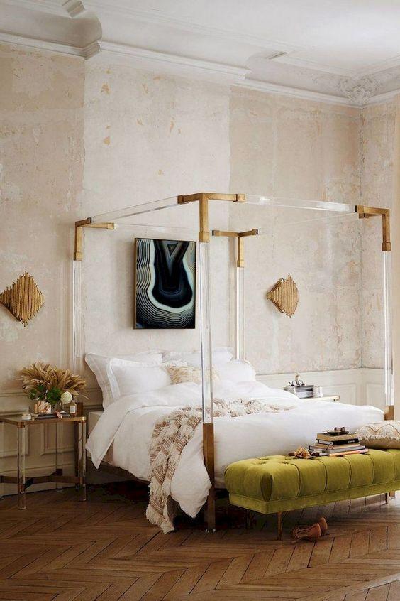 una camera da letto parigina creativa con un letto accattivante con cornice in acrilico, una panca verde, opere d'arte accattivanti e pareti arrossate