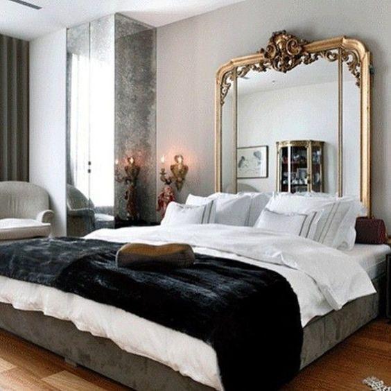 uno spazio parigino chic con un'affascinante testiera a specchio, un grande letto, pannelli a specchio e una lampada antica
