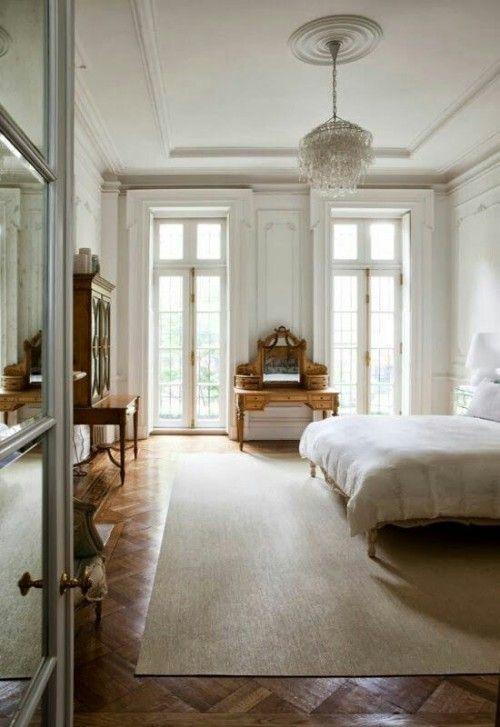 una camera da letto parigina neutra con mobili antichi in legno, un lampadario di cristallo e grandi finestre per riempire lo spazio di luce