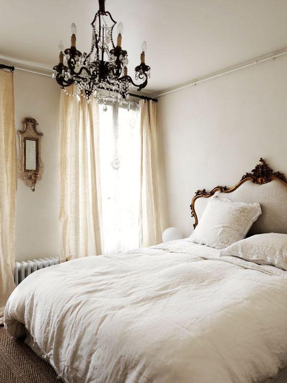 una camera da letto parigina neutra con un letto raffinato, un lampadario di cristallo, uno specchio e drappeggi fluidi