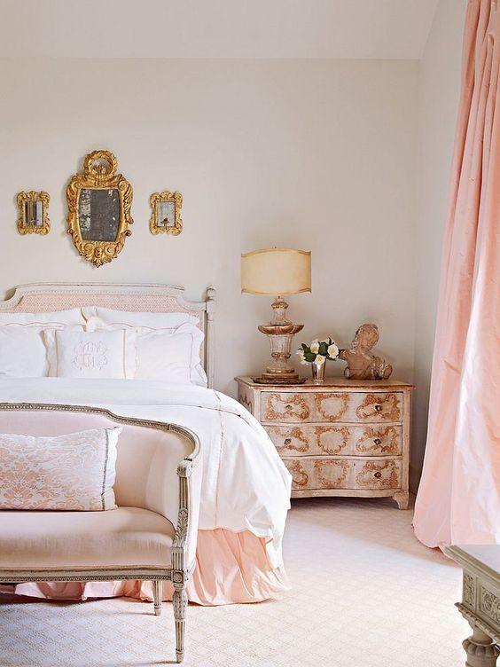 una camera da letto parigina da sogno in tonalità neutre e arrossate, con una disposizione di specchi, raffinati mobili vintage con intarsi dorati