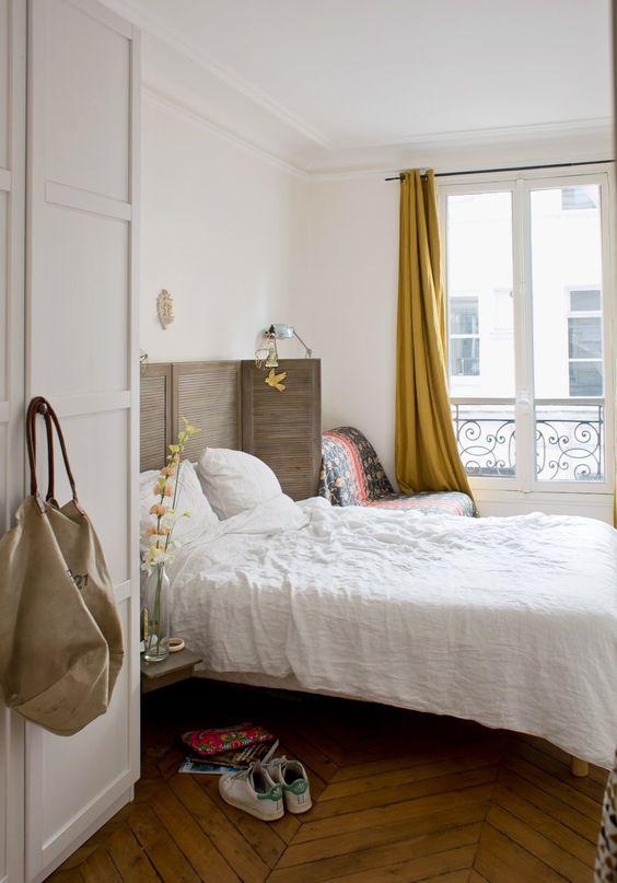 una camera da letto chic ispirata a Parigi con uno schermo otturatore come testiera, un pavimento a spina di pesce, tende senape e una comoda sedia