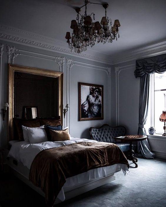 una camera da letto raffinata e lunatica con un lampadario di tendenza, opere d'arte, stucoo, una testiera imbottita scura e mobili sofisticati