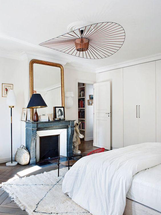 una camera da letto parigina neutra con un caminetto blu non funzionante, una lampada d'effetto, uno specchio chic e un'antica sedia in legno