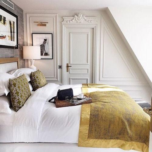 una piccola camera da letto parigina mansardata con opere d'arte, un letto comodo, lampade e stucchi per decorare le pareti