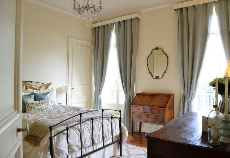 una romantica camera da letto parigina con mobili antichi in legno, un letto di metallo, tende blu polvere, un lampadario di cristallo è pieno di luce