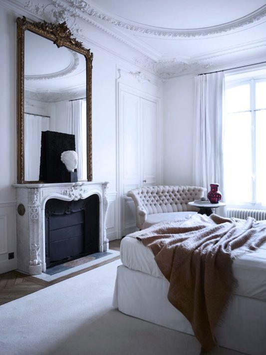 una camera da letto parigina bianca con uno specchio sopra il camino, un letto imbottito, un divano trapuntato chic e molta luce naturale