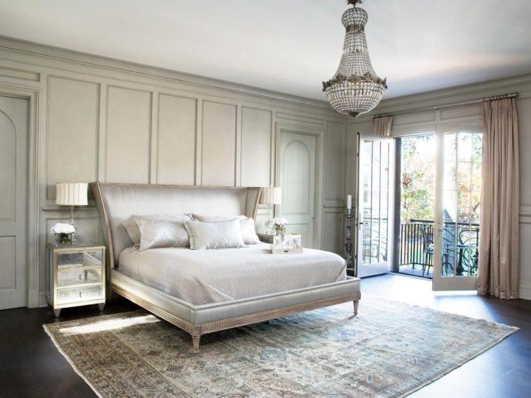 una camera da letto parigina molto elegante con un tappeto stampato, un letto imbottito chic, un lampadario di cristallo e comodini a specchio