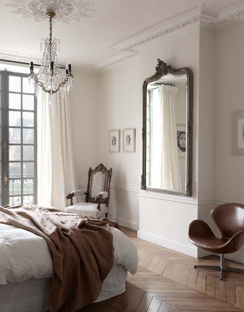 un'elegante camera da letto parigina con pavimento a spina di pesce, uno specchio di tendenza, un lampadario di cristallo chic e una sedia raffinata