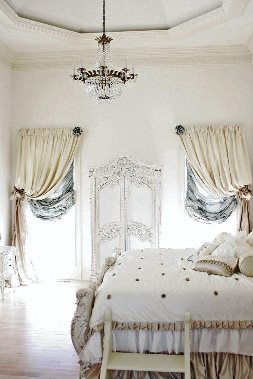 una camera da letto parigina di ispirazione antica in colori neutri e morbidi tocchi di blu, con mobili sofisticati e tendaggi chic