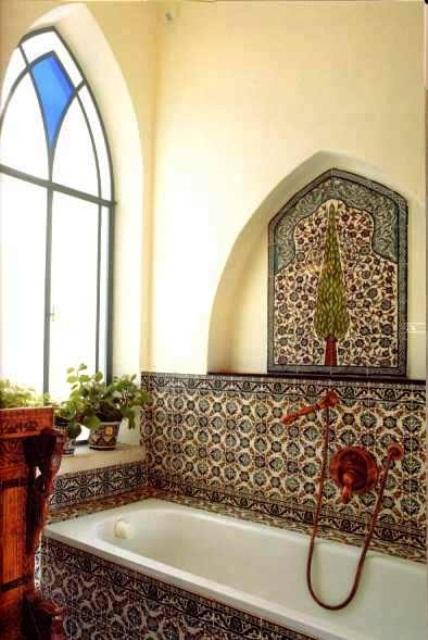 un luminoso spazio marocchino con piastrelle marocchine, una finestra a mosaico, piante in vaso e hardware in rame scuro