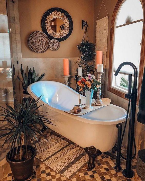 un bagno boho con vasca con piedini, candele, piante in vaso, cesti decorativi e uno specchio decorato