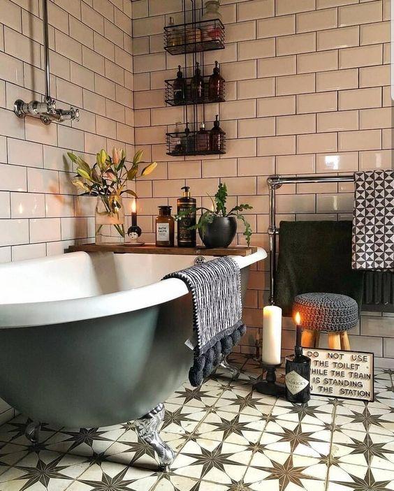 un bagno boho fatto con graziose piastrelle marocchine, piante e fiori in vaso, candele e una vasca verde con i piedini