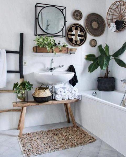 un bagno boho con cesti decorativi, un tappeto all'uncinetto, cesti per la conservazione e piante in vaso
