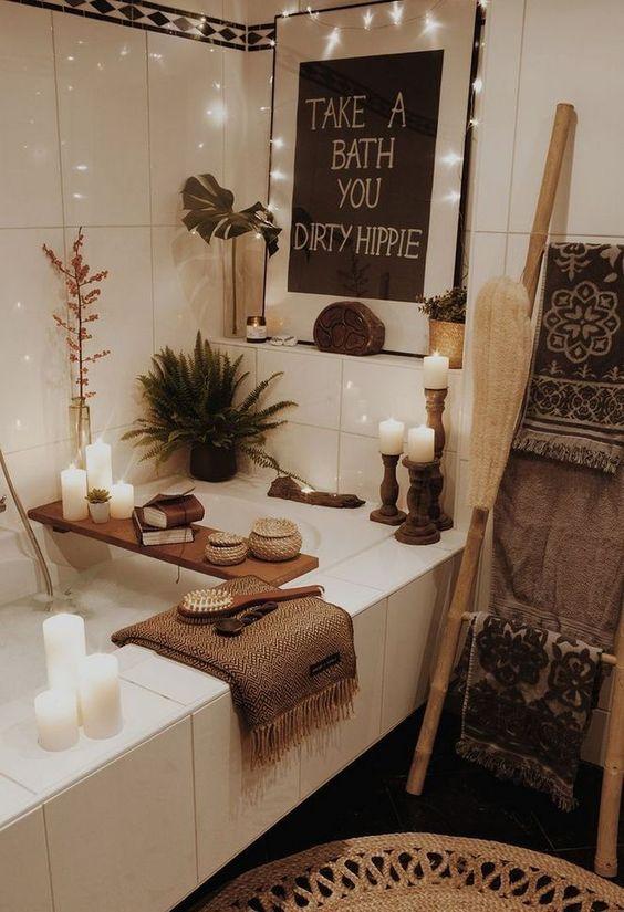 un bagno boho con luci, un'opera d'arte, un contenitore di legno, molte candele e tocchi di iuta