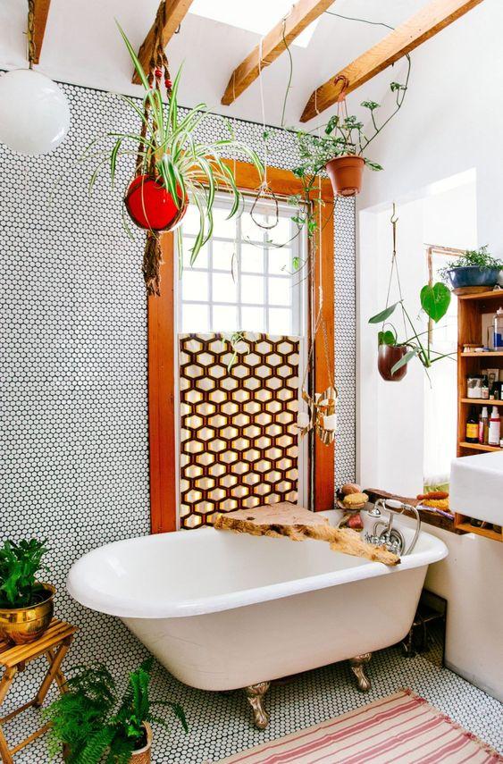 un bagno boho fatto con piastrelle penny, uno schermo geometrico, vegetazione in vaso, una vasca con i piedini e un caddy bordo vivente