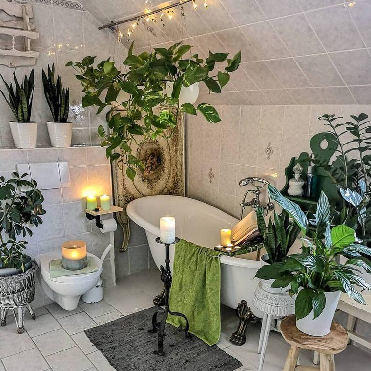 un'oasi boho con molta vegetazione in vaso, candele, luci e una vasca da bagno con i piedini e cestini