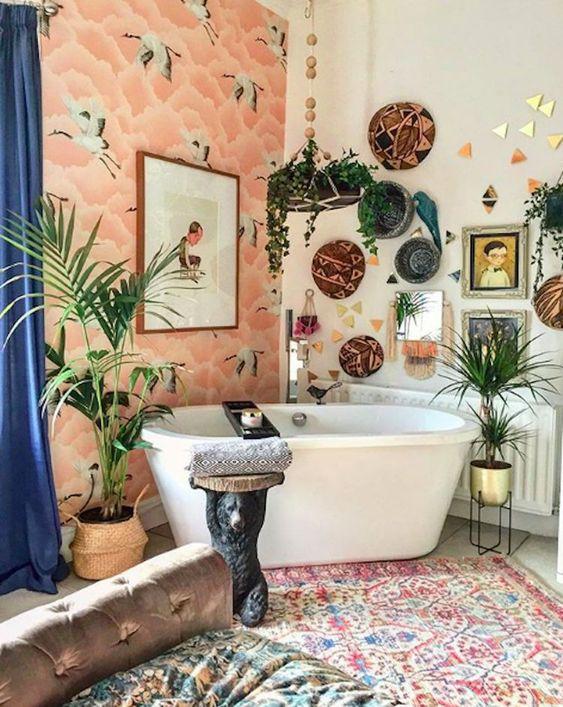 un bagno luminoso con un muro di carta da parati, tappeti boho, cesti decorativi, piante in vaso e opere d'arte