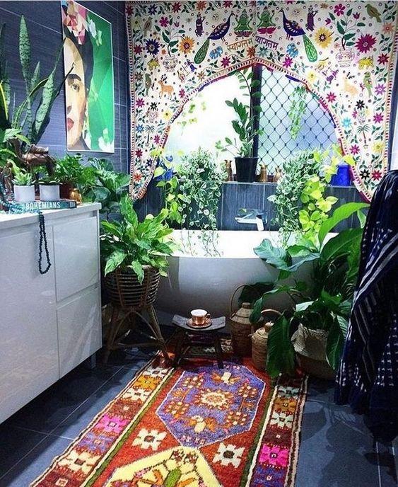 un bagno marocchino boho con una tenda colorata, un tappeto luminoso e opere d'arte e molta vegetazione in vaso