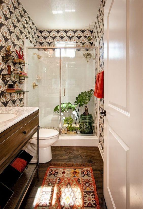 un boho incontra un bagno art déco con carta da parati accattivante, un tappeto boho, vegetazione e un tavolino dipinto