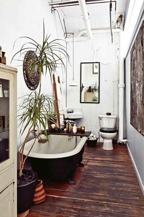 un boho incontra un bagno rustico con un pavimento macchiato, una vasca nera, piante in vaso, un cesto decorativo, elettrodomestici vintage