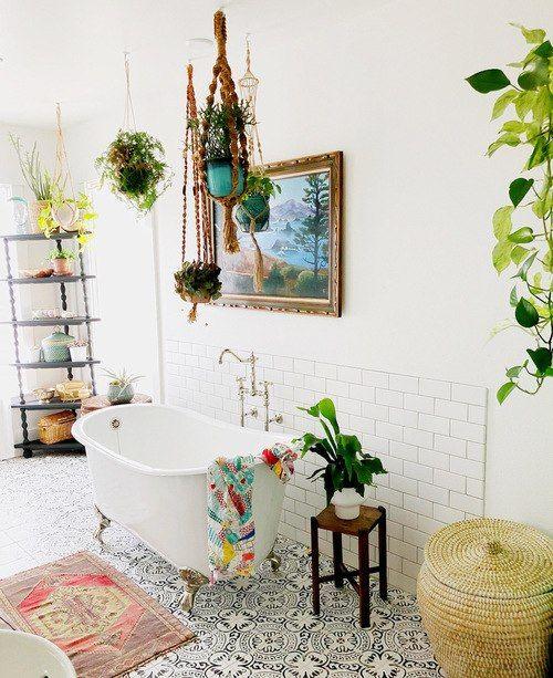 un luminoso bagno boho con pavimento in piastrelle a mosaico, tappeti e asciugamani boho, pianta in vaso, vasca con piedini e un etagere