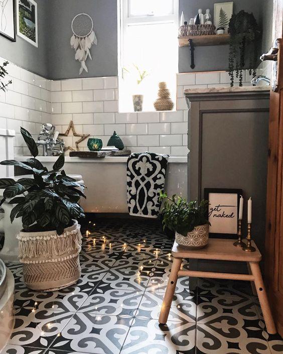 un bagno boho monocromatico con tessere di mosaico, metropolitana bianca, acchiappasogni, piante in vaso, luci e una vasca