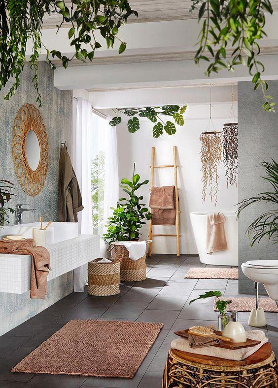 un contemporaneo incontra lo spazio boho con piante in vaso, cestini, mobili in rattan, uno specchio di vimini e una scala