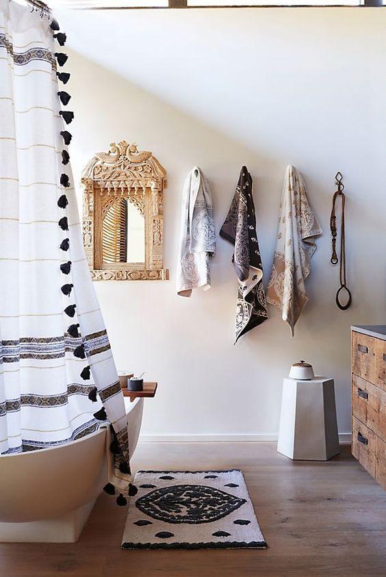 un bagno neutro con un tappeto boho, una tenda con nappe, asciugamani stampati e uno specchio decorato
