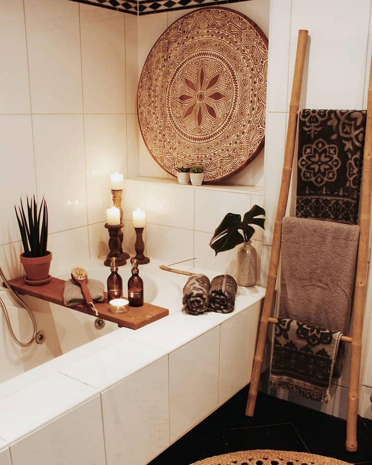 un bagno neutro con un vassoio decorativo, piante in vaso e candele, una scala con asciugamani stampati e un tappeto di iuta