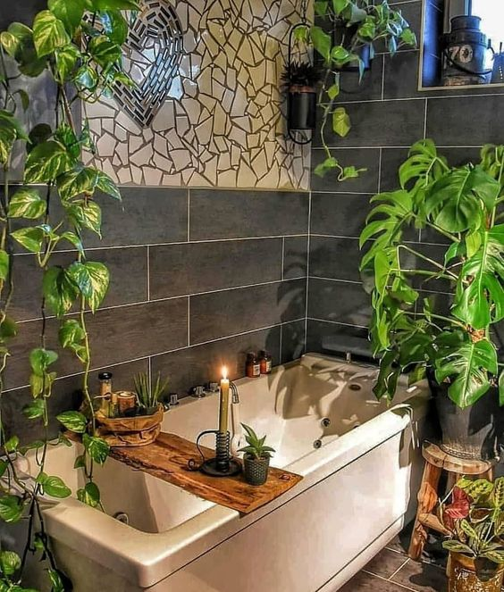 un elegante bagno boho con mosaici sul muro, piante in vaso, un contenitore di legno e candele