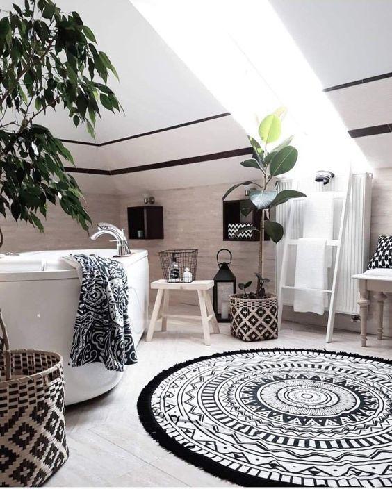 un bagno boho monocromatico con tessuti stampati e cesti fantasia, piante, una vasca e lanterne