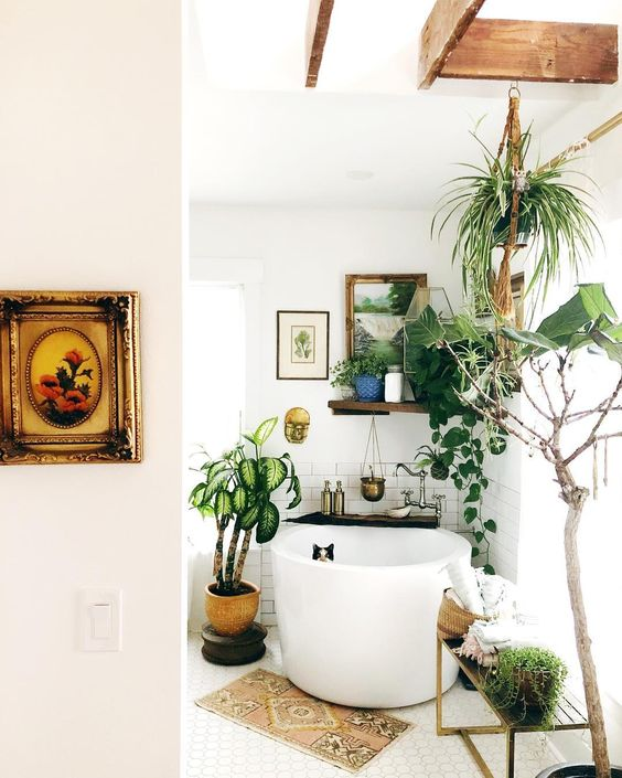 un piccolo bagno boho con una vasca da bagno, un tappeto boho, piante in vaso e opere d'arte