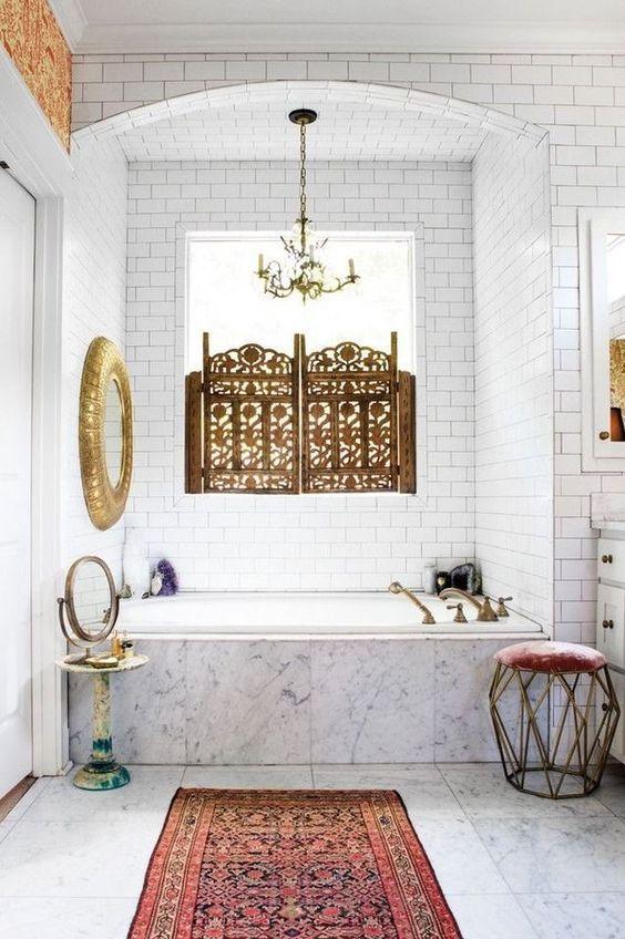 un bagno neutro con un'atmosfera marocchina, uno specchio dorato, un tappeto boho, un bellissimo schermo alla finestra e uno sgabello geometrico