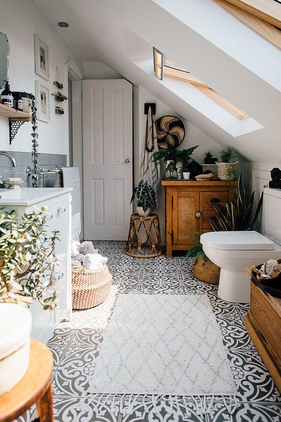 un bagno boho mansardato con un armadietto in legno, un tavolino in rattan, un cesto e alcune piante in vaso