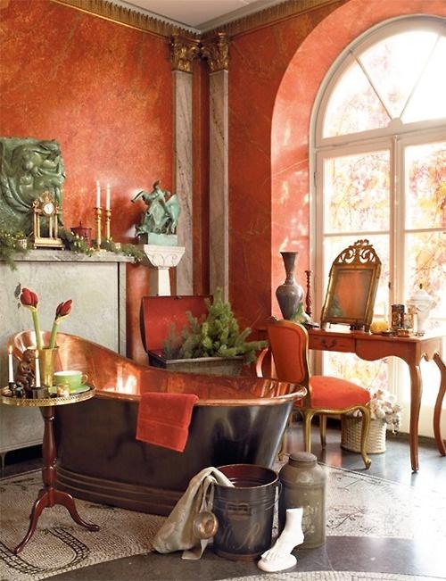 un elegante bagno vintage con pareti in gesso rosso, una vasca nera e rame, sculture chic e una consolle vintage