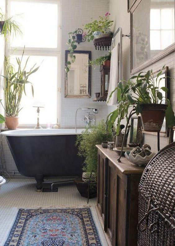 un bagno boho vintage con vasca nera, piante in vaso, un armadietto colorato e un tappeto boho