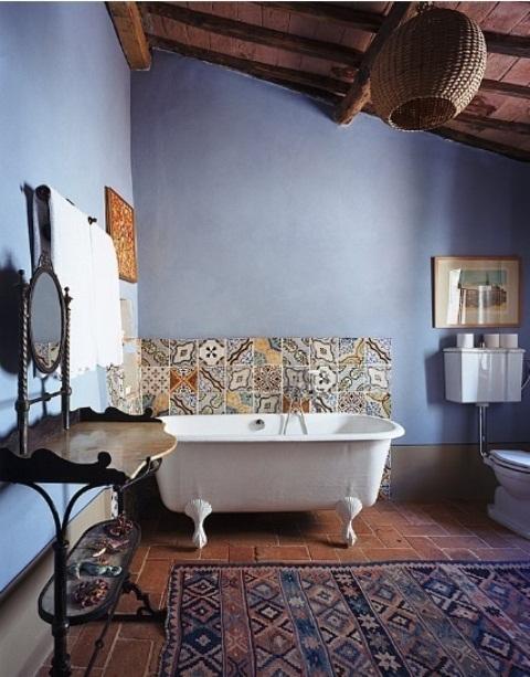 un bagno boho vintage con pareti blu, una vasca con i piedini, tappeti boho e piastrelle marocchine, una vanità in legno intagliato e uno specchio decorato