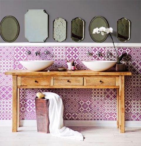 un luminoso bagno boho con piastrelle stampate viola, un lavabo in legno e una disposizione di specchi marocchini