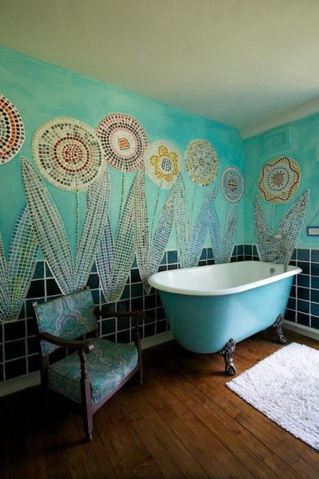 un bagno creativo con pareti turchesi realizzate con mosaici floreali per un'atmosfera di spirito libero, una vasca luminosa con i piedini e una sedia vintage
