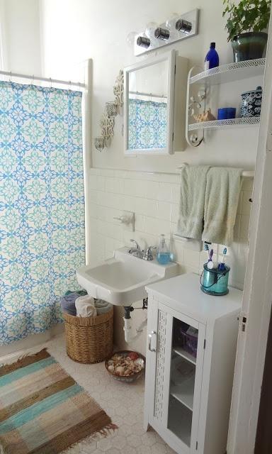 un bagno bianco con vari mobili, tessuti boho per un tocco di colore