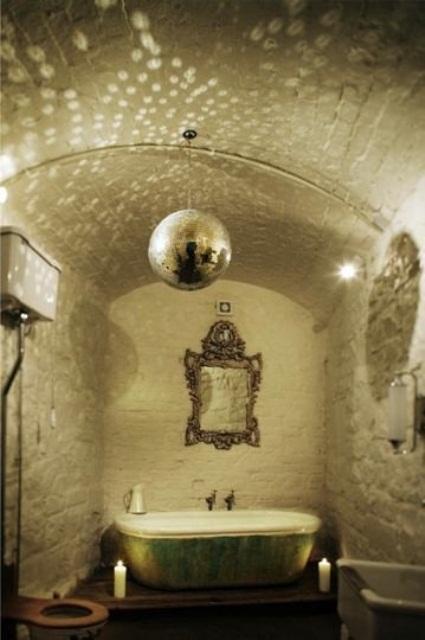 un bagno bianco unico con una vasca da bagno shabby chic verde, uno specchio decorato, una lampada scintillante e candele