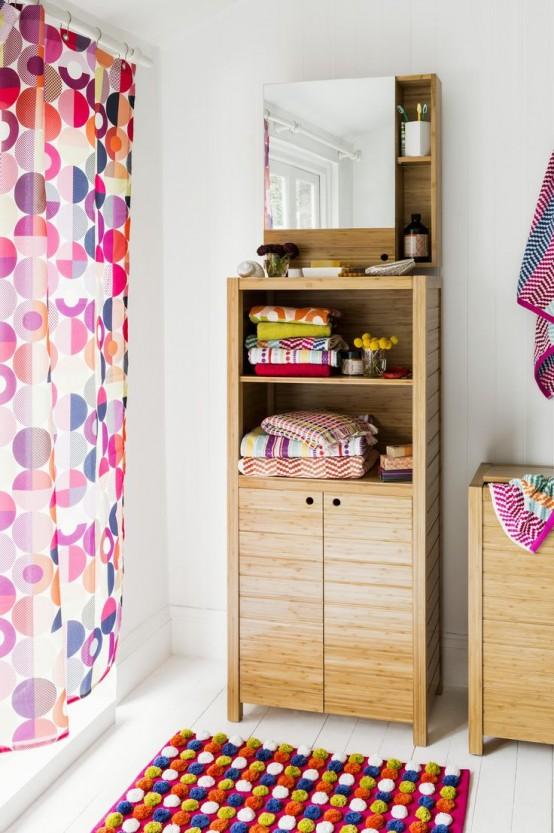un bagno neutro con mobili in legno chiaro, una tenda colorata e un tappeto più asciugamani luminosi