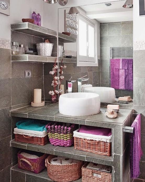 un bagno grigio rivestito con piastrelle tipo sotne e con asciugamani luminosi e altri tessuti