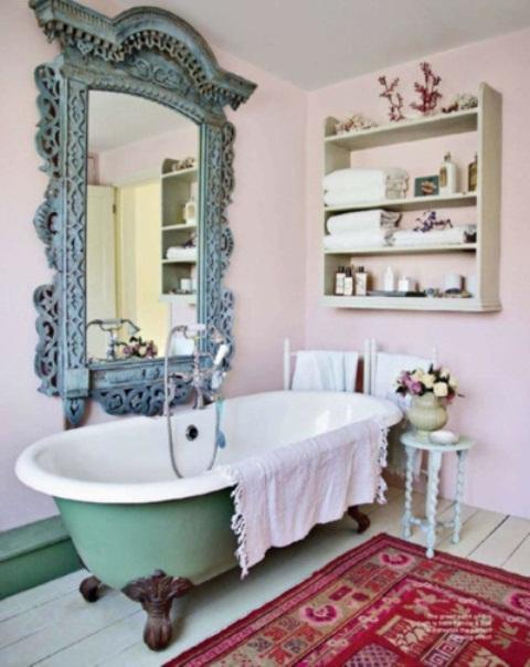 un bagno rosa con una vasca verde con i piedini, tappeti boho, un grande specchio decorato in una cornice blu e una mensola