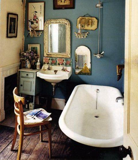 un bagno vintage con pareti blu, una vasca autoportante, una galleria a parete e opere d'arte oltre a mobili vintage
