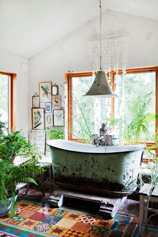 un bagno vintage boho con piastrelle colorate, una vasca da bagno shabby chic, molta vegetazione in vaso e una galleria a parete