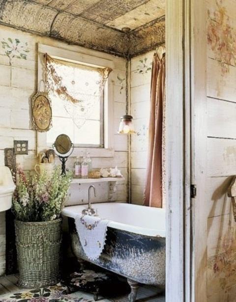 un bagno shabby chic con pareti a battente, specchi, una vasca con i piedini, tappeti florla e un cesto con fiori