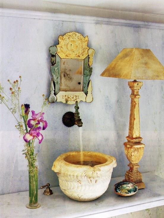 uno spazio balneare unico con un lavandino in pietra scolpita, uno specchio decorato, una lampada chic e una composizione floreale