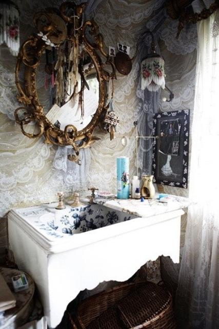 un bagno raffinato con tende di pizzo, un lavabo in legno intagliato, uno specchio decorato e arazzi in macramè